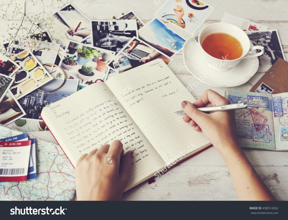 stock-photo-writing-travel-diary-memories-photos-concept-458514262
